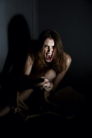 Human trafficking. Concept. Exhausted woman shouts at camera Stock Photo