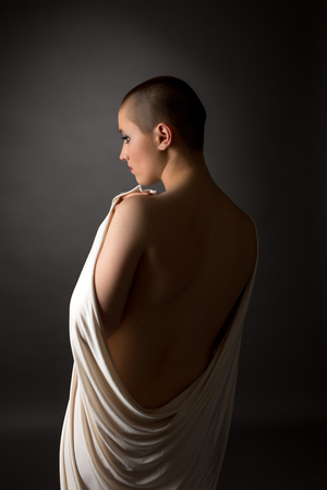 Rear view of defenseless woman with shaved head, on grey background