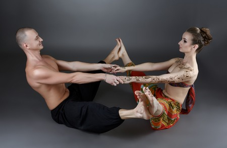 sexual position: Yoga with partner. Professional trainers show one of asanas