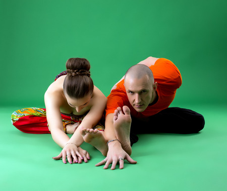 sexual position: Paired yoga training. Instructor looking attentively at camera Stock Photo