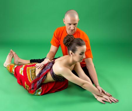 position d amour: Yoga. entra�neur exp�riment� aide femme pour effectuer asana Banque d'images