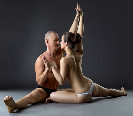 nude male body: Sexual yoga. Seminude partners posing close to each other Stock Photo