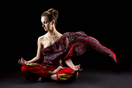 Beautiful calm woman meditates in lotus position and her sari flying