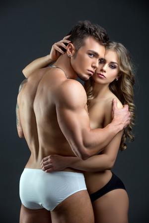 topless: Studio photo of beautiful heterosexual couple hugging at camera Stock Photo