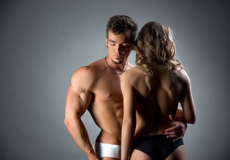 sexy topless woman: Image of muscular hunk embracing topless model by waist