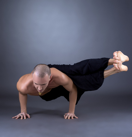 nude yoga: Studio photo of middle-aged man practicing yoga at camera Stock Photo