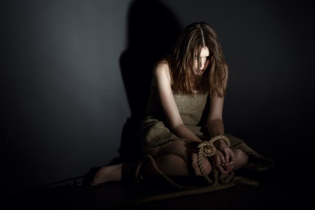 bondage girl: Kidnaping concept. Image of exhausted model with tied hands