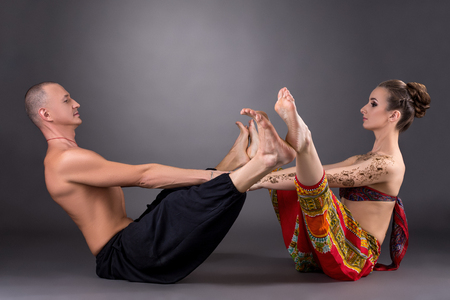 sexual position: Studio photo of man and woman doing yoga together