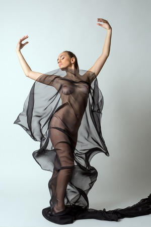 Nude woman gracefully dancing with transparent cloth Stock Photo