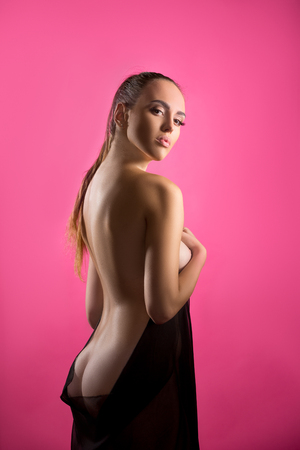 topless brunette: Photo of sexy brunette posing nude at camera, on pink background Stock Photo