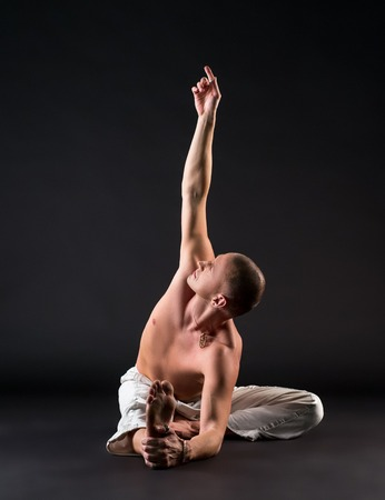 nude yoga: Image of bare-chested man doing yoga in studio, on grey background