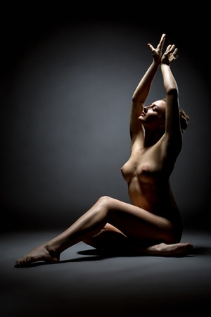 erotic woman: Elegant female dancer posing nude at camera, on grey background