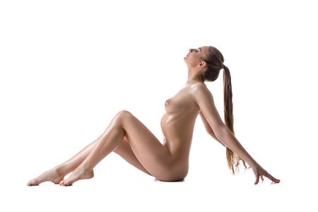 femmes nues sexy: Vue de côté d'une jeune fille nue avec de longs cheveux rassemblés en queue de cheval