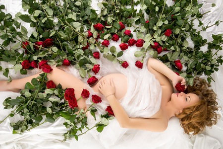 mujer con rosas: Vista superior de la mujer embarazada que presenta en cama con las rosas