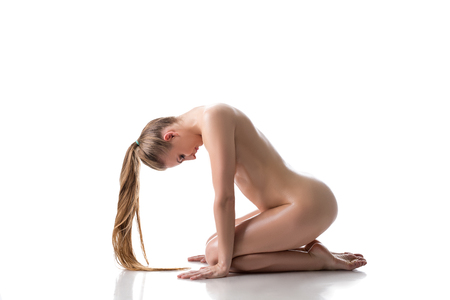 Side view of nude pretty woman posing with her head bowed