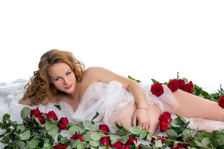 naked belly: Red-haired pregnant woman posing among red roses in studio Stock Photo