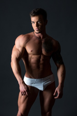 naked male body: Studio photo of handsome blue-eyed guy with fit body Stock Photo