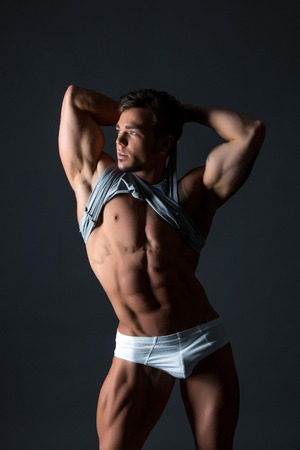 erotic male: Studio photo of hot blue-eyed bodybuilder shows his body