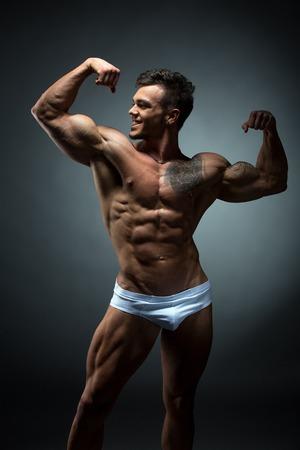 nudo maschile: Foto dello studio di bodybuilder sorridente ammira il suo bicipite