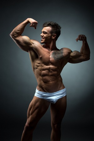 nude male body: Studio photo of smiling bodybuilder admires his biceps