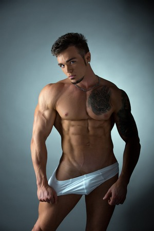 erotic male: Sexy tattooed bodybuilder posing in provocative pose Stock Photo