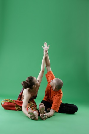 asana: Yoga. Man and woman performing paired asana, on green background