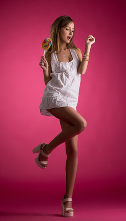 Flirtatious girl in nightie posing with candy, on pink background