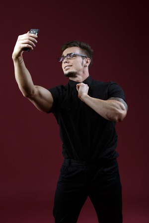 narcissist: Image of stylish young guy doing selfie in studio