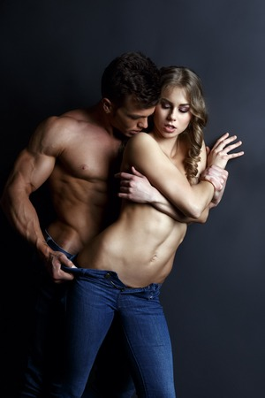topless jeans: Erotica. Photo of passionate muscular guy strips sexy girl