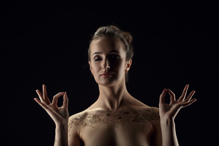 modelos desnudas: Yoga. Desnuda meditando mujer, con las manos en mudra. Aislado en el fondo negro