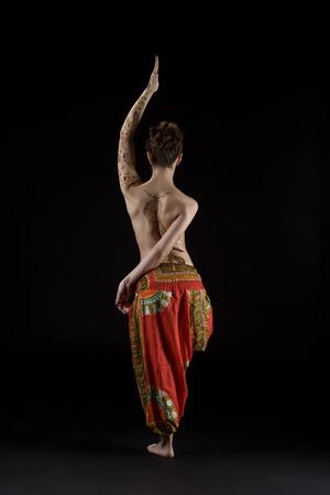 naked young women: Йога. Студия фото топлес женщина делает асаны, обратно в камеру Фото со стока