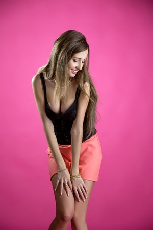 Image of seductive young coquette smiling at camera, on pink background