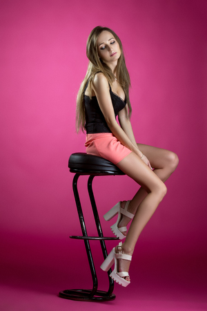 Sexy young fashionista sitting on high bar stool