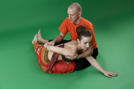 sexual position: Experienced yoga instructors while doing asana. Studio photo, on green background