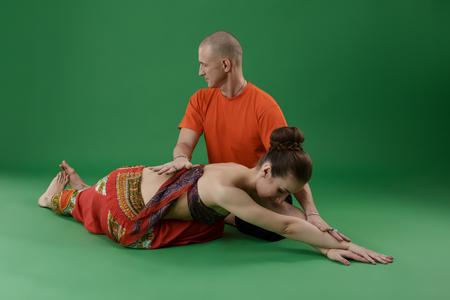 position d amour: Yoga. Femme faisant asana et instructeur en regardant � son Banque d'images