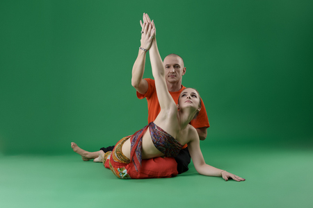 asana: Yoga. Studio photo of instructor helps woman to perform asana Stock Photo