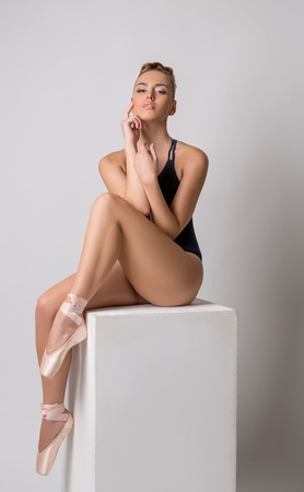 Photo of sensual ballet dancer posing sitting on cube Stock Photo