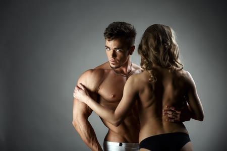 sexy topless women: Studio photo of bodybuilder hugs topless model, on gray background