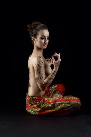seins nus: Yoga et mehndi. Belle femme aux seins nus m�dite en studio Banque d'images
