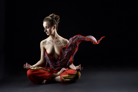 nude young woman: Yoga. Image of sensual woman meditating in lotus position