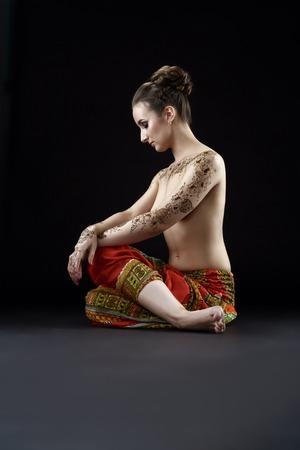 topless: Studio photo de femme aux seins nus avec des motifs de henn� sur le corps