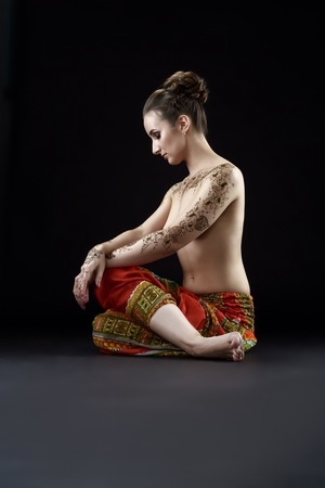 topless brunette: Studio photo of topless woman with henna patterns on body