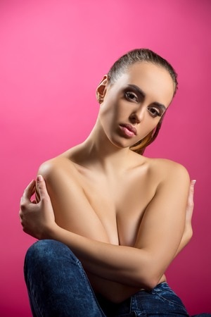 brunette naked: Studio image of beautiful brunette hugging herself, on pink background