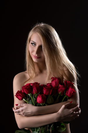 topless model: Nice topless blonde posing with bouquet of roses, on black backdrop