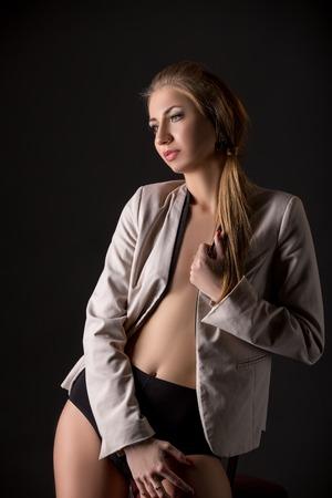 junge nackte mädchen: Attractive model posing in jacket and panties. Studio photo