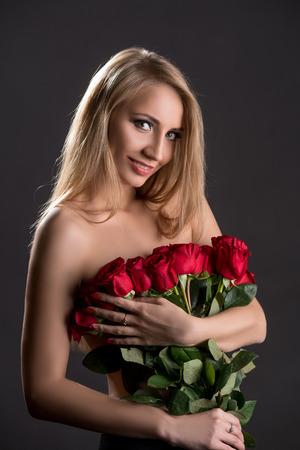 seins nus: Sourire blonde posant torse nu avec bouquet de roses Banque d'images