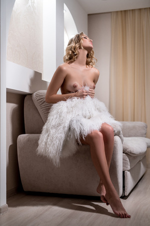 nude blonde woman: Image of sexy nude model with fur sitting in hotel room Stock Photo