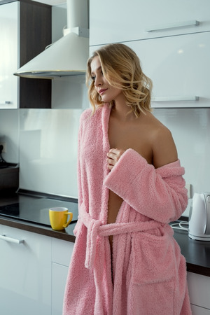 Relaxed sexy blonde posing on kitchen in early morning