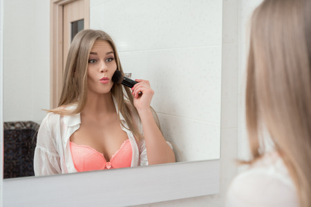 ropa interior ni�as: Reflection in mirror of funny model applying powder