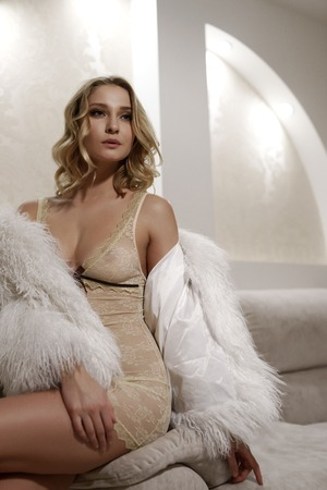 Glamorous model posing in erotic negligee and faux fur